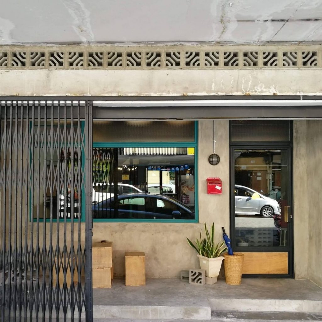 Exterior of Specialty Coffee Cafe Ampersand in Kota Kinabalu, Malaysia. Industrial cement finish with accordion shutter gate and makeshift wooden furniture.