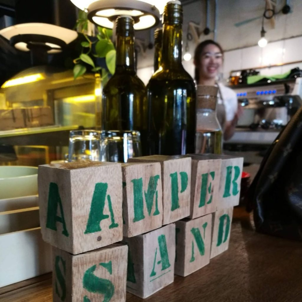 Wooden blocks spell out the cafe name at the counter. Barista is smiling. Specialty Coffee Cafe interior design of Ampersand in Kota Kinabalu, Malaysia.
