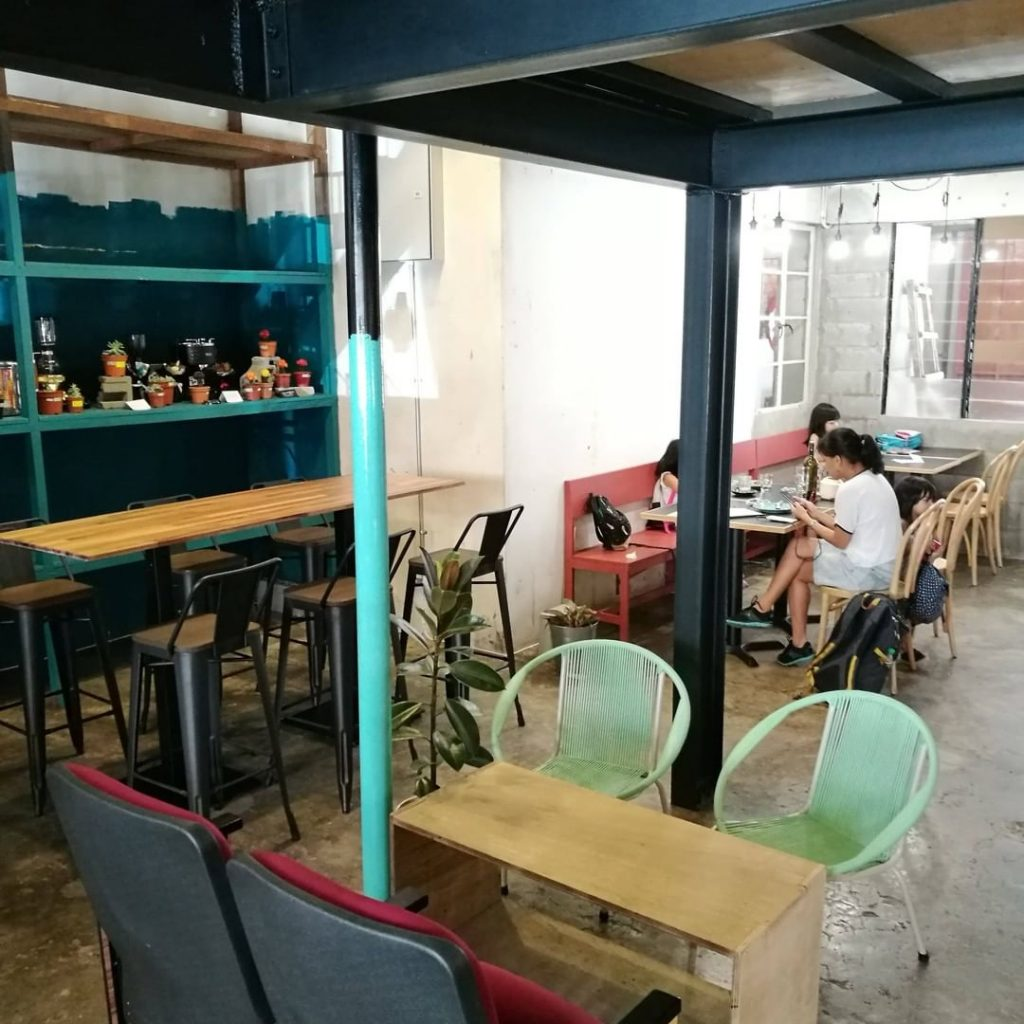 Eclectic mix of mismatched tables and chairs. Specialty Coffee Cafe interior design of Ampersand in Kota Kinabalu, Malaysia.