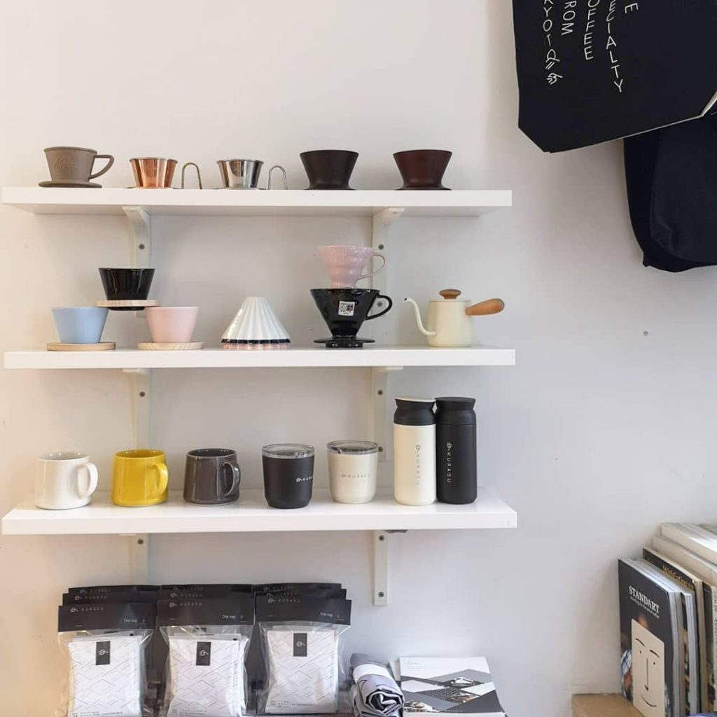 Various coffee equipment rest on top of three white shelves arranged on a white wall.