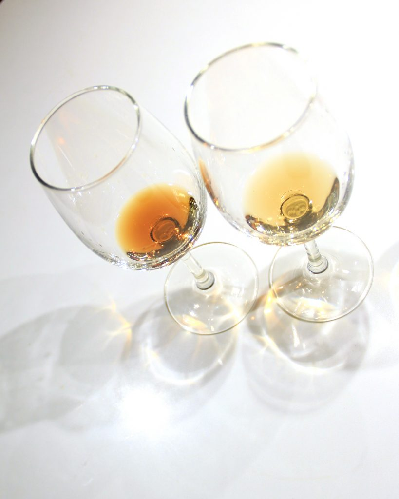 Top view of two wine glasses placed side by side on a white table, and filled with very small amounts of rum.
