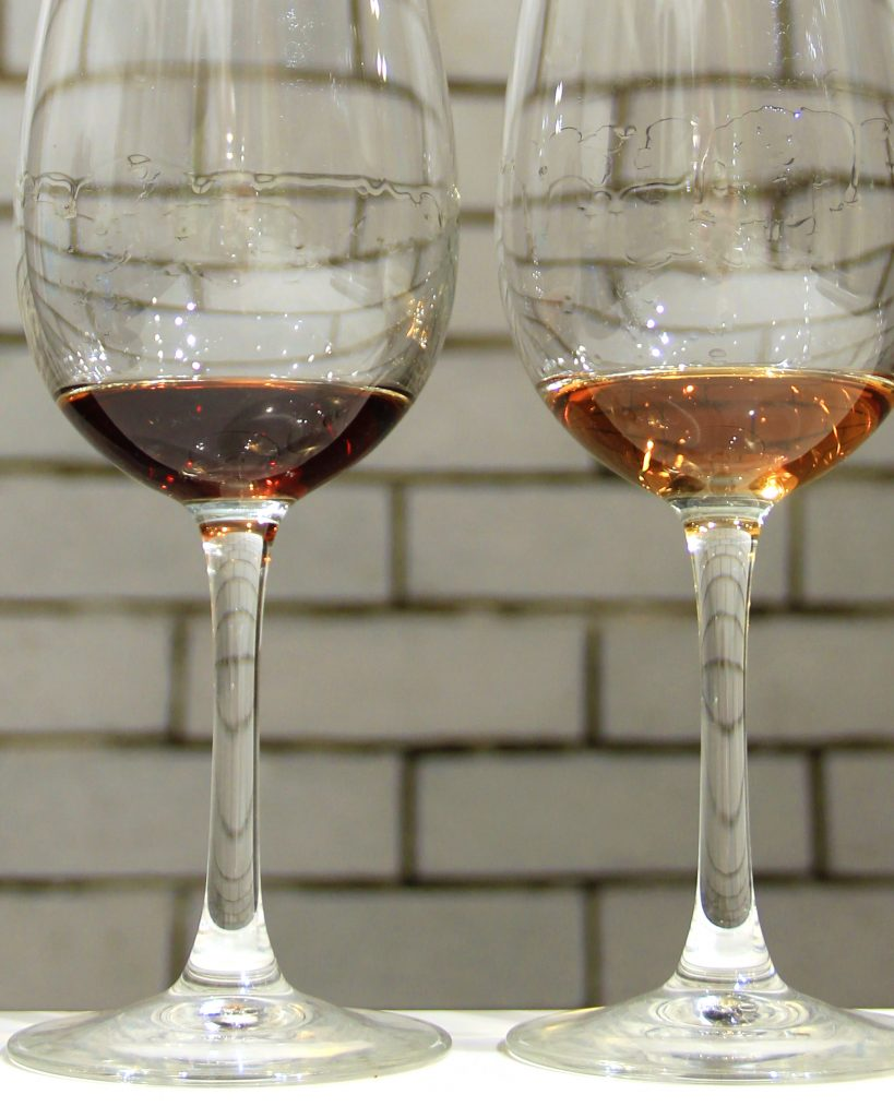 Closeup lateral shot of two wine glasses placed side by side in front of a grey brick backdrop. Both wine glasses are filled with small amounts of rum.