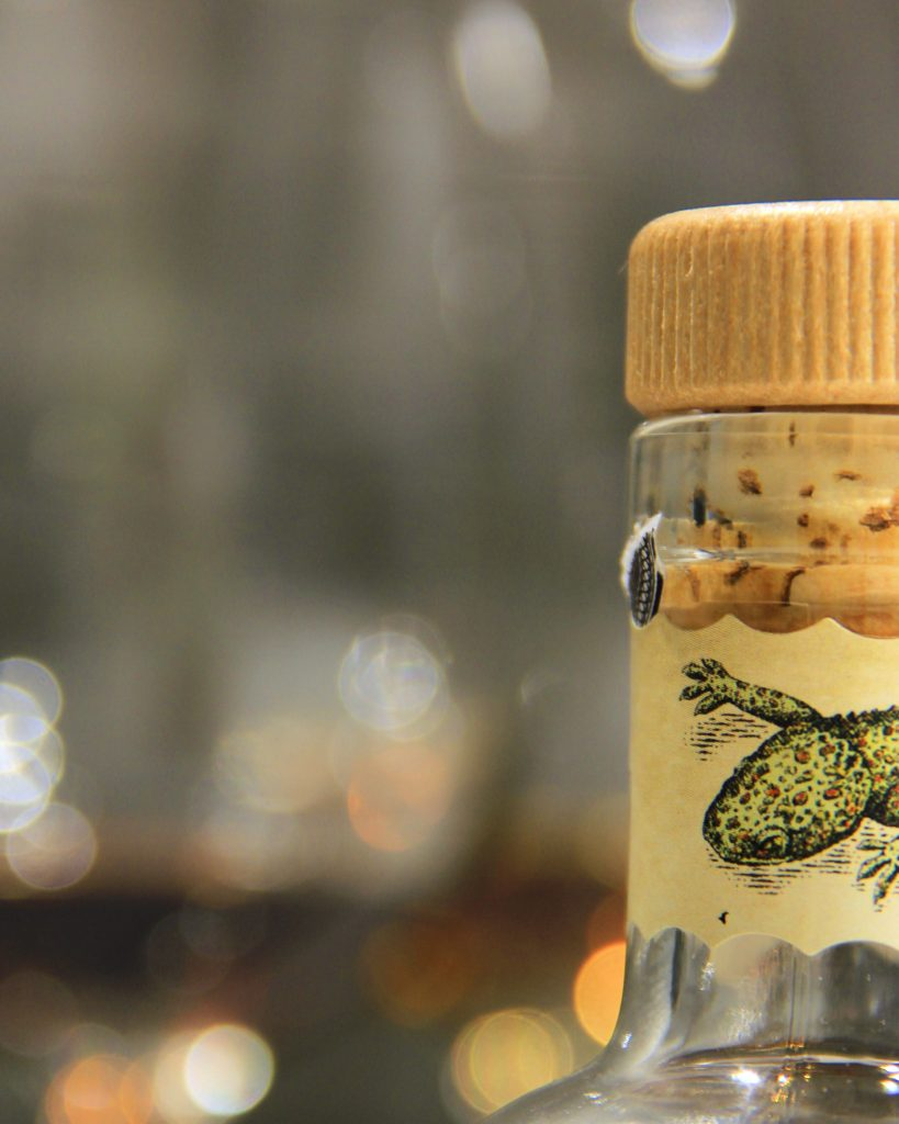 Extreme closeup shot of a rum bottle's neck, aligned to the right of the photo. A label is wrapped around it, decorated with a green lizard head peeking from the right side of the photo.