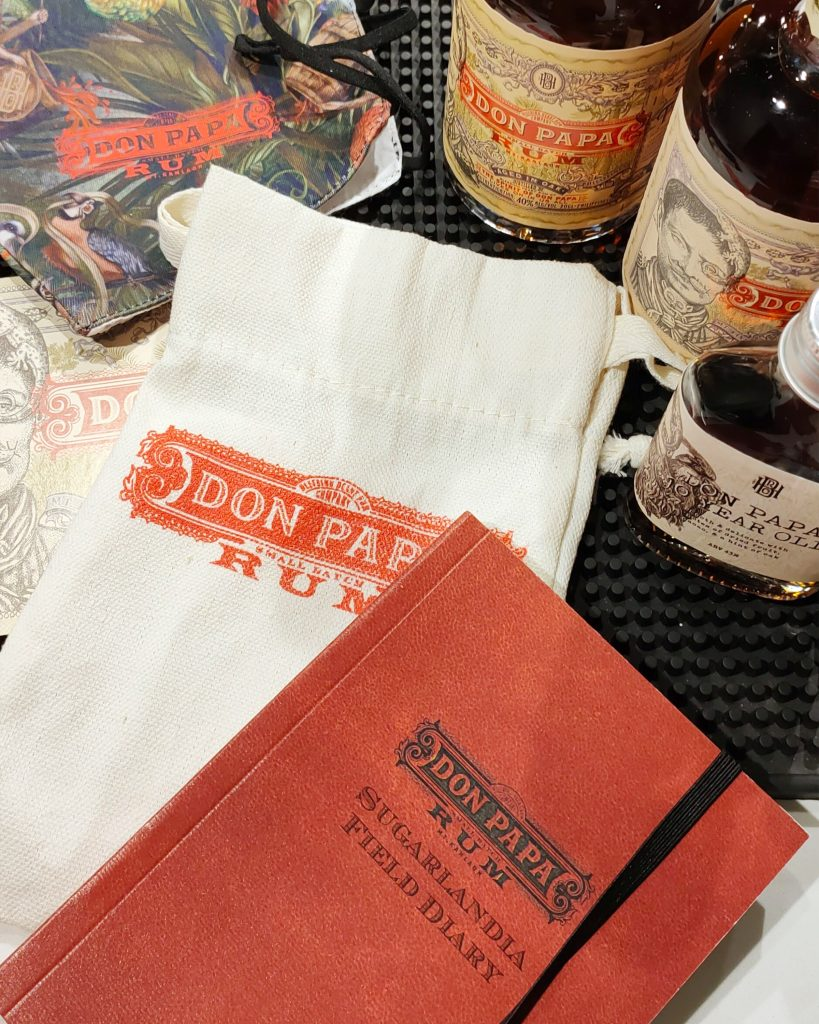 Top shot of three bottles of Don Papa Rum, arranged decoratively with a collection of Don Papa merchandise: a tote bag, a notepad, and a journal.