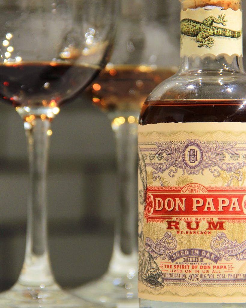 Closeup shot of a bottle of Don Papa Rum, with two wine glasses blurred in front of a grey brick backdrop.