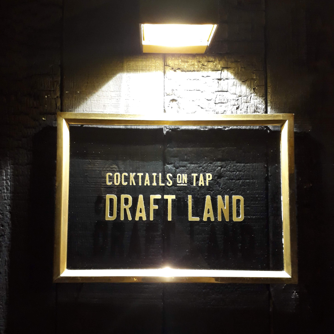 """A picture of Draftland's simple glass panel sign. The words, """"Cocktails on tap, Draftland"""" is written in gold letters. The glass panel is installed in a gold frame, and is hanging on stone wall, illuminated by an overhead light."""