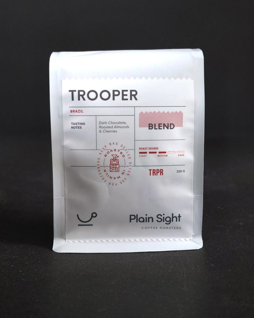 One bag of Plain Sight Coffee's Trooper varietal, front-facing with a black backdrop. Silver tall packet with minimalist label accented with red elements.