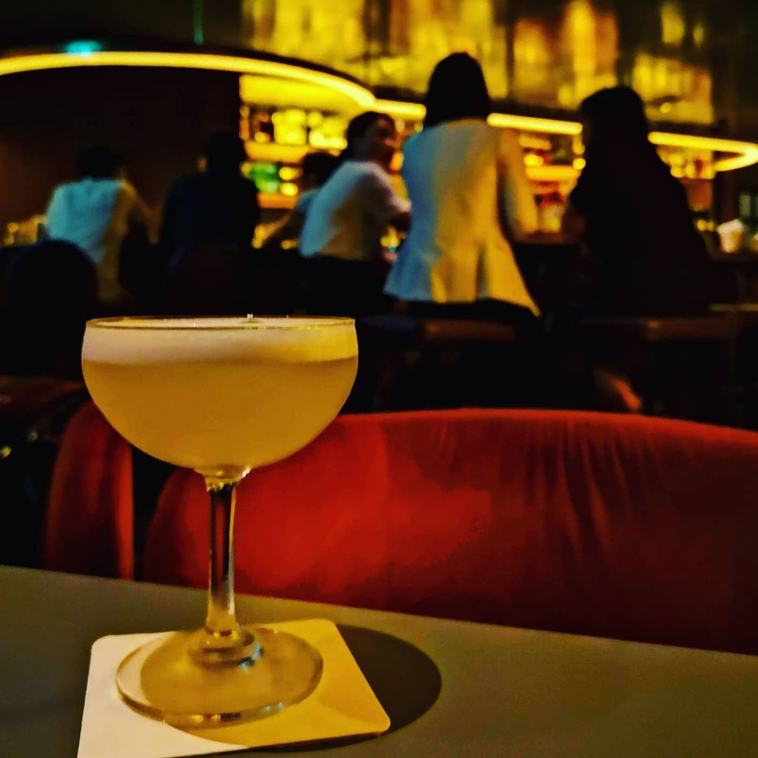 A cocktail glass filled with Jigger & Pony's alcohol-free cocktail, Apple Elderflower. It is placed on top of a white square coaster with rounded edges. Behind the glass, patrons of the bar can be seen talking animatedly among one another. The scene is illuminated by yellowish-orange lights.