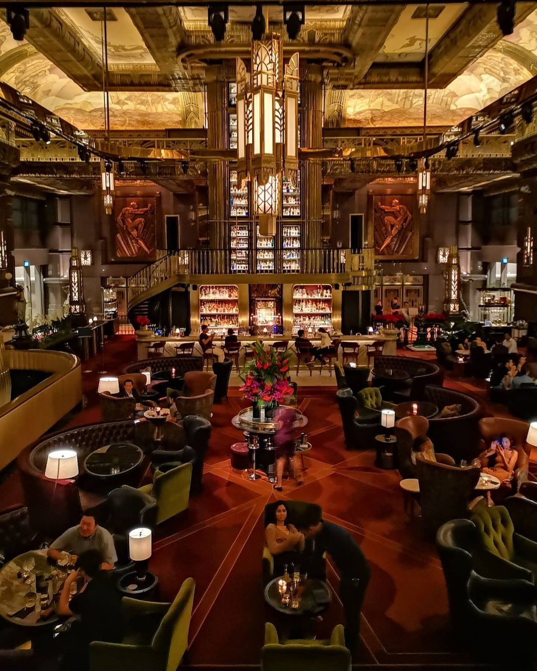 A photo of Atlas's interior, taken from a high vantage point. The European art deco aesthetic is apparent. A red carpet with straight geometric designs covers the floor. Leather-lined chairs and tables are arranged neatly on top of the floor. The well-illuminated bar near the center of the massive room seems to have no bartender. Atlas seems to be at 75% capacity. Art-deco-inspired chandeliers hang from the similarly-inspired ceiling, illuminating the area below.