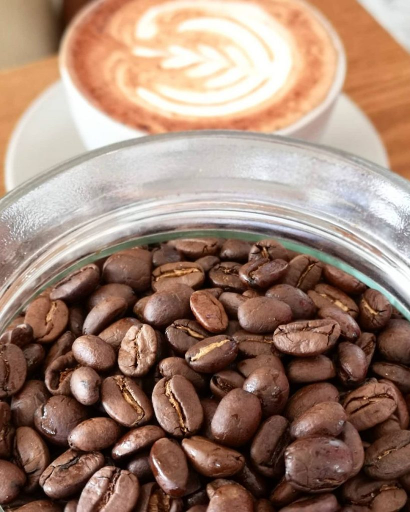 A closeup shot of coffee beans in a glass bowl, in front of a latte serving as the background.