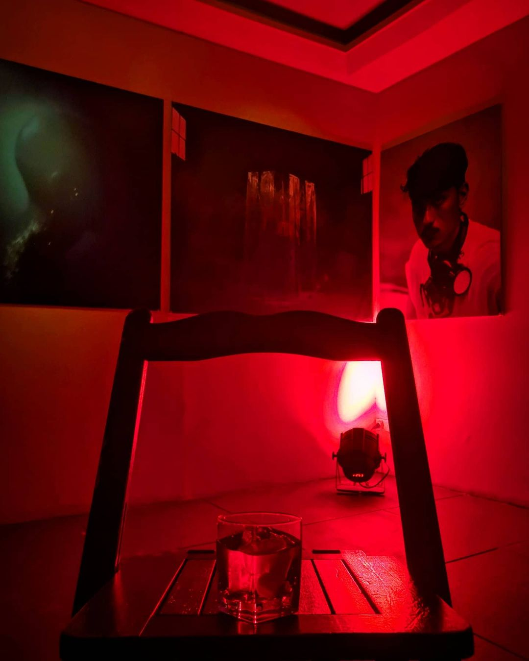 A glass of negroni sits on top of a wooden table in the middle of a room fully-saturated by red light. The walls of the room are adorned with three paintings. Welcome to Limbo.