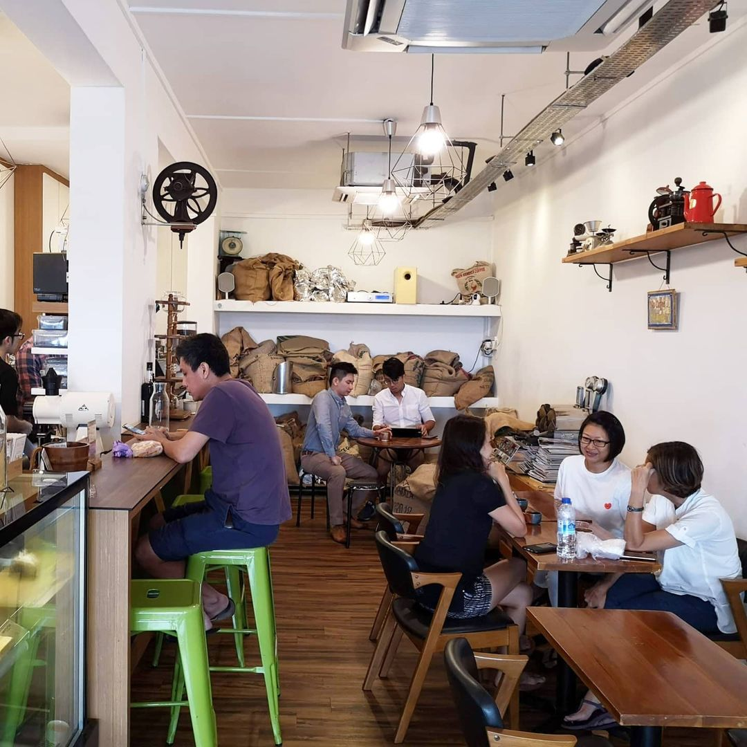 A photo of Tiong Hoe Specialty Coffee's interior. The chairs, tables, floor, and bar are made predominantly of wood, with the exception of green stools serving as bar chairs. Several brown burlap sacks sit on top of three tiers of shelves occupying the entirety of the background wall. The lone barista behind the bar serves six customers: one sitting in front of the bar, three by the long table to the right of the photo, and two by the round table in front of the burlap sacks.