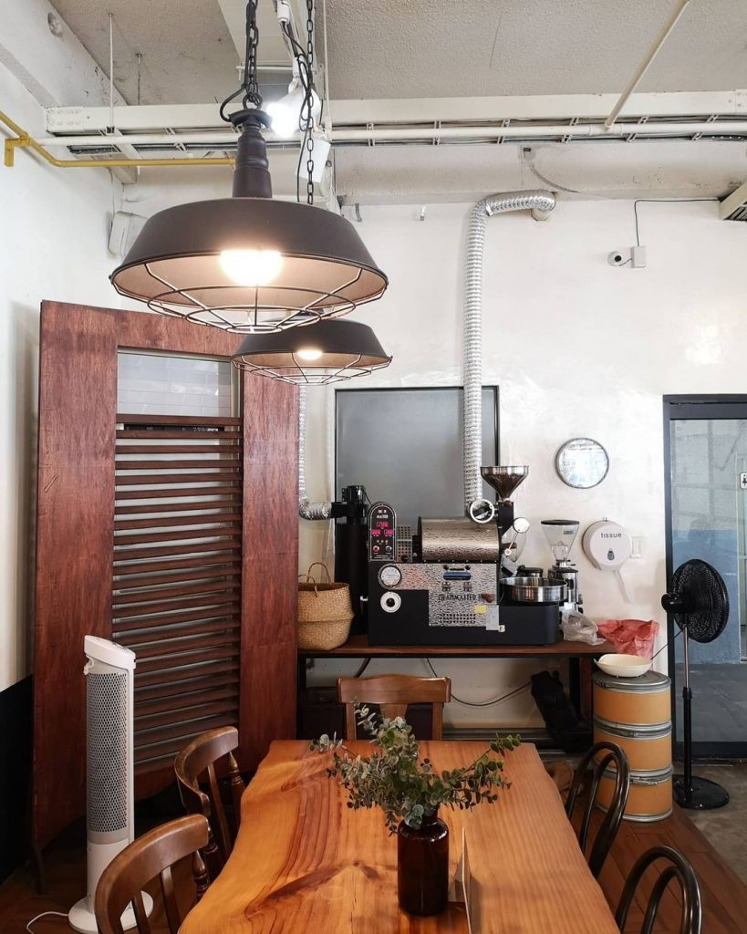 A shot of Cafe Dia's interior. Two lamps hang from the ceiling by metal chains. A coffee roasting machine sits on top of a wooden table against the back wall, beside a black electric fan. On the foreground, an irregularly-shaped wooden table is flanked by chairs of different materials. On top of this table is a glass vase with an ornamental plant. To the left of the image, beside the table, is a standing air conditioner.