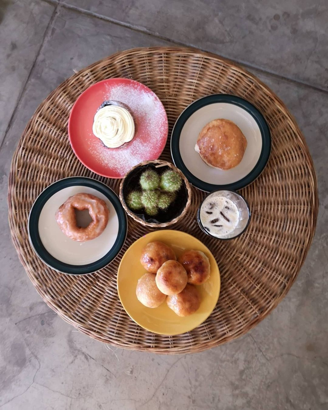 A top shot of a basket with a selection of Masa Bakery's pastries. On the center of the basket is a small cactus in a pot, surrounded by four plates of varying sizes and colors. One each plate is a different kind of pastry. In between two of these plates is a glass filled with beverage.