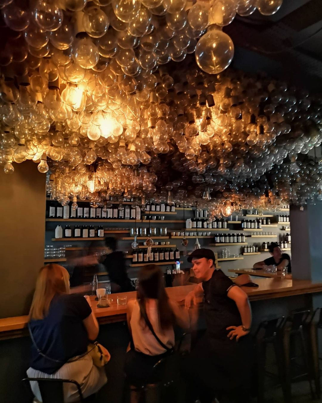 A shot of Operation Dagger's interior. In the foreground, three people can be seen sitting in front of the wooden bar, with another person sitting on the far right end. The bartender is busy making a drink behind the bar, facing a gray wall that's covered with several wooden shelves full of neatly-arranged bottles. The scene is illuminated by several lightbulbs hanging down the ceiling, which cannot be seen due to the sheer number of bulbs covering it.