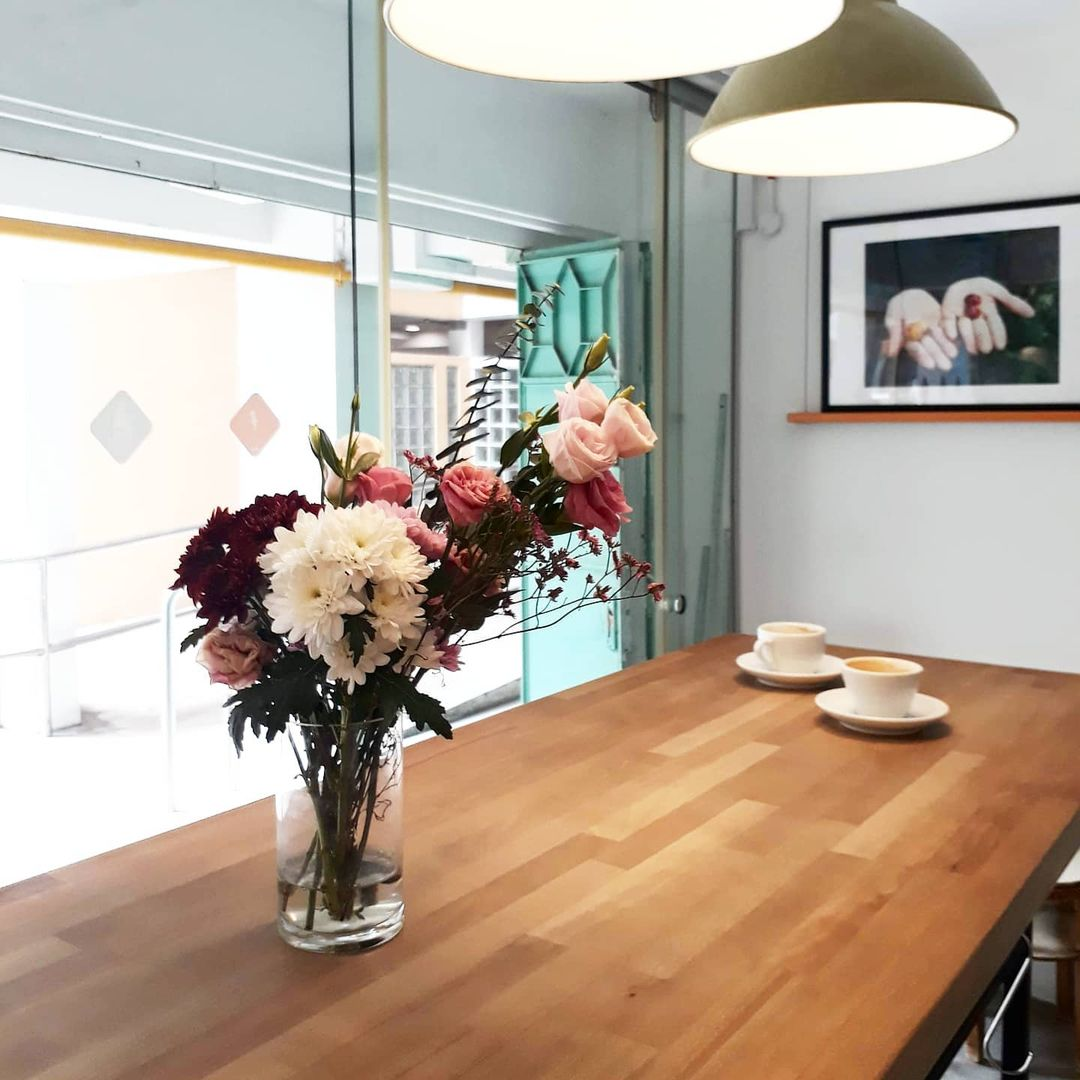 A picture of Nylon Coffee's interior. Two coffee cups and a vase sit on top of a long wooden standing table, situated beside a window. The room's white wall is adorned by a framed photograph of two hands each holding coffee fruits. The entire scene is illuminated by two hanging lamps.
